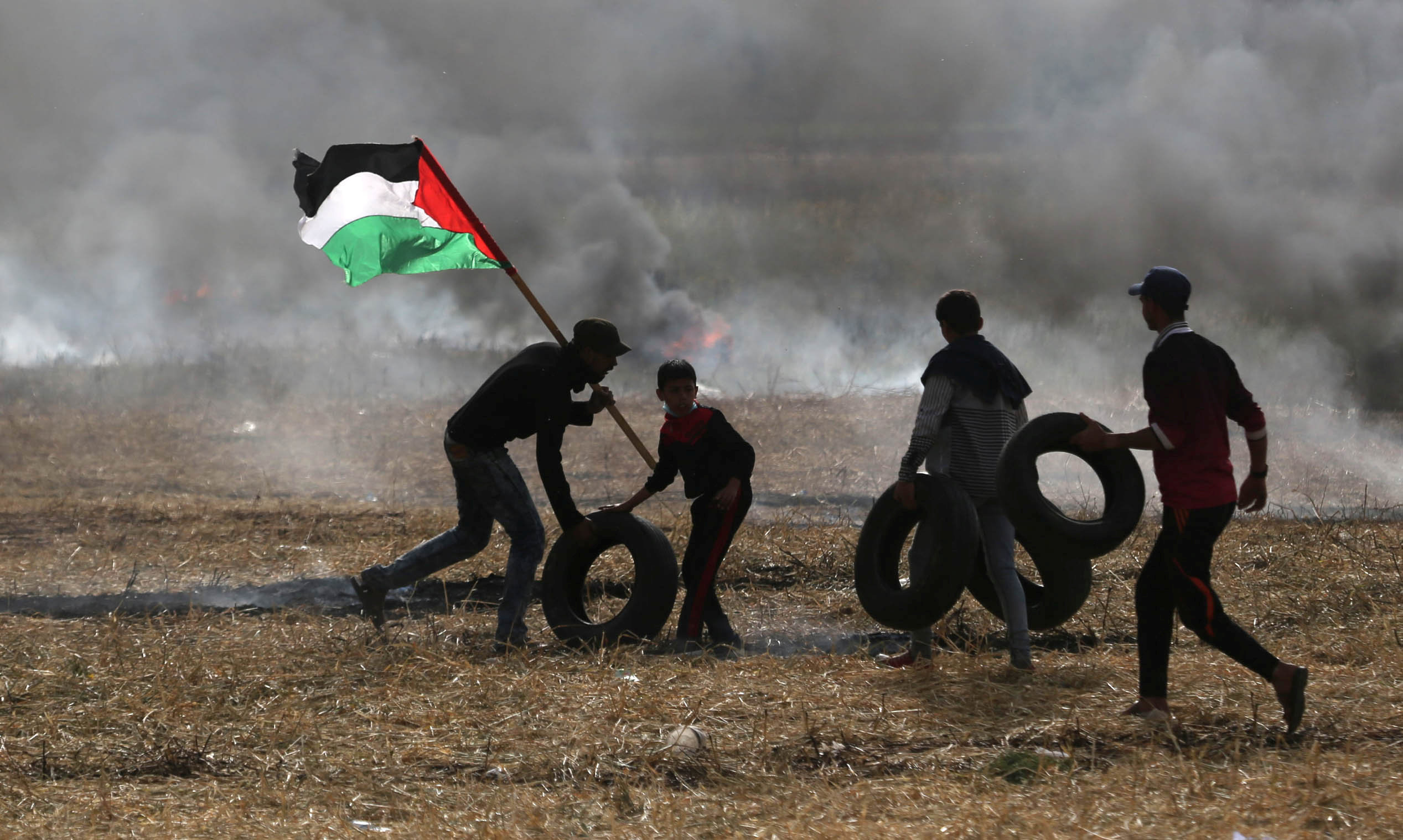Palestinian protesters carry tires to burn them during clashes with Israeli troops at Israel-Gaza border, in the southern Gaza Strip April 5, 2018. REUTERS/Ibraheem Abu Mustafa