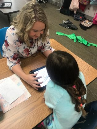 Former Oklahoma teacher Chelsea Price, 34, helps a 2nd grade student with an assignment on an iPad in her classroom in Grapevine, Texas, U.S., April 4, 2018. Courtesy Chelsea Price/Handout via REUTERS