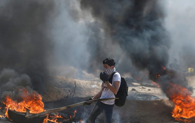 A Palestinian passes burning tires during clashes with Israeli troops at a protest demanding the right to return to their homeland, at the Israel-Gaza border east of Gaza City April 6, 2018. REUTERS/Mohammed Salem