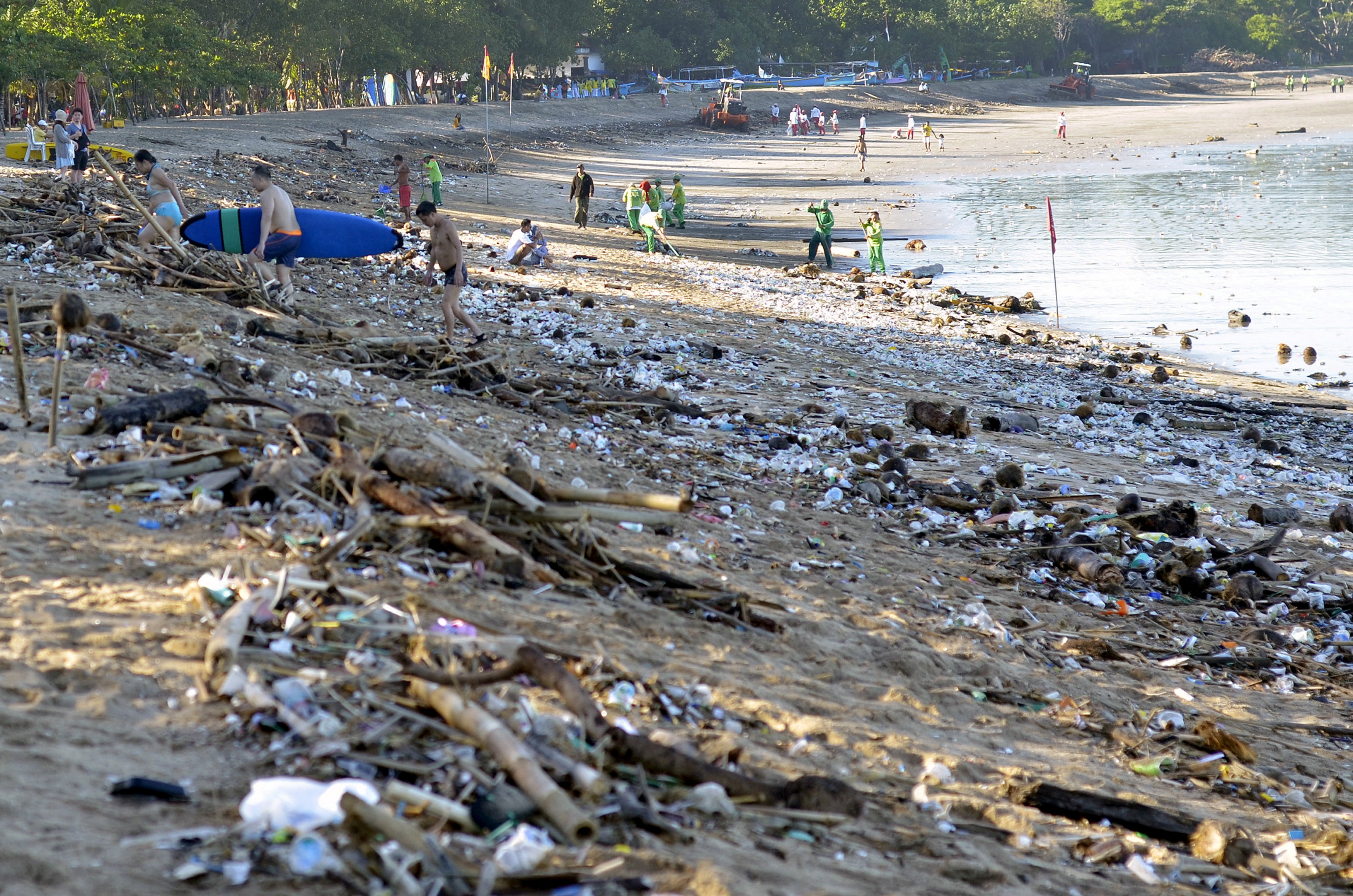 FILE PHOTO: Tourists walk amongst trash washed up on Kuta beach by seasonal winds, as workers attempt a clean-up in the background, on the Indonesian island of Bali February 15, 2016 in this photo taken by Antara Foto. REUTERS/Wira Suryantala/Antara Foto