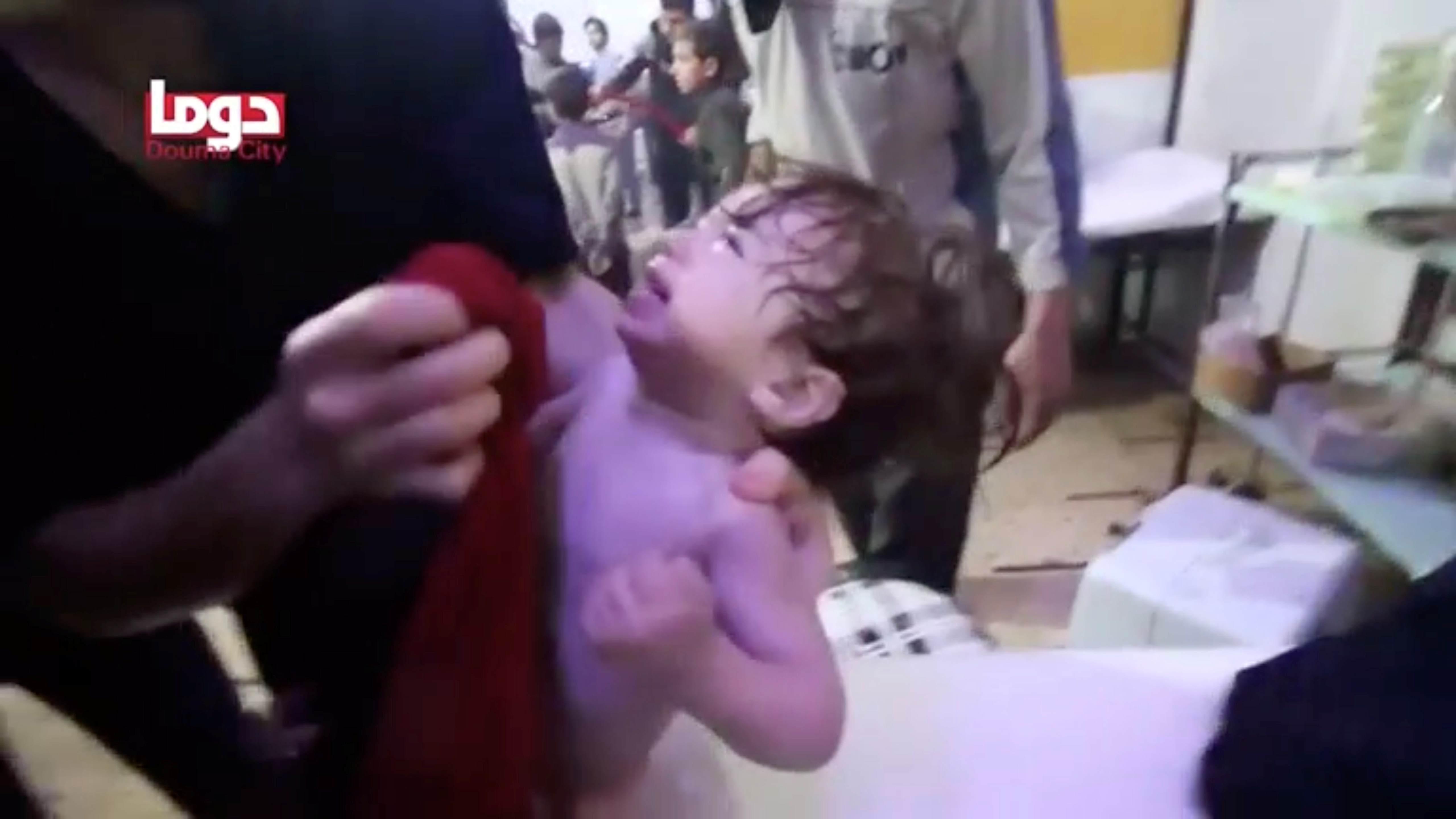 A child cries as they have their face wiped following alleged chemical weapons attack, in what is said to be Douma, Syria in this still image from video obtained by Reuters on April 8, 2018. White Helmets/Reuters TV via REUTERS