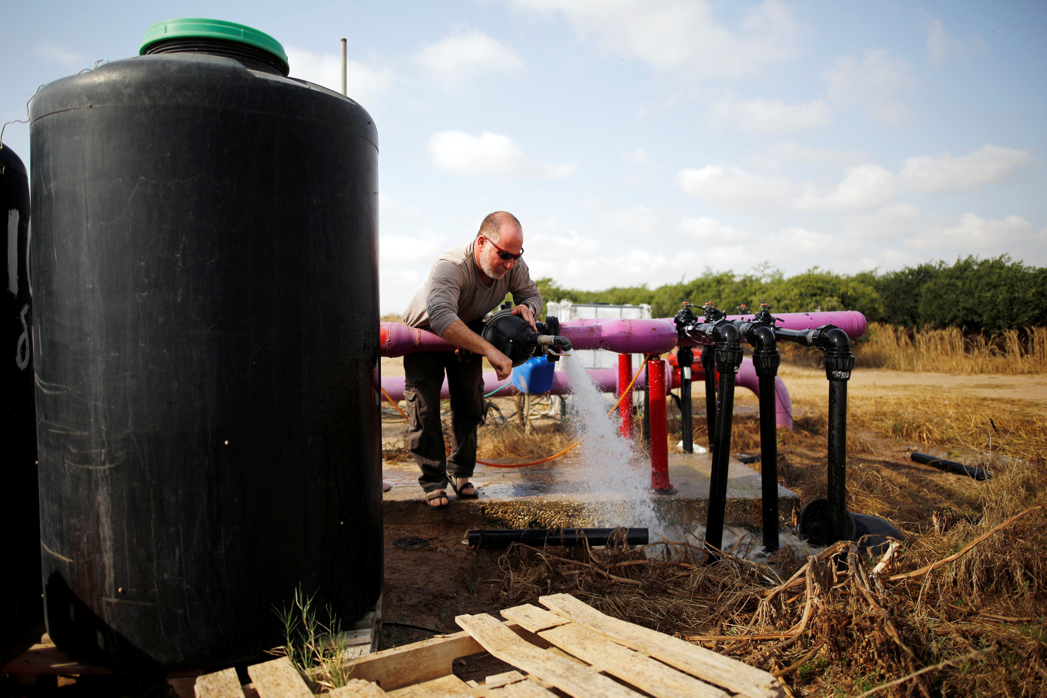 A farmer tends to a water faucet in a field in Kibbutz Nahal Oz, near the Gaza Strip border, Israel April 8, 2018. REUTERS/Amir Cohen