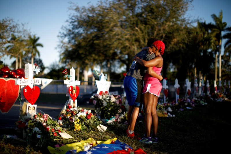 Adin Chistian (16), student of the Marjory Stoneman Douglas High School, embraces his mother Denyse, next to the crosses and Stars of David placed in front of the fence of the school to commemorate the victims of a shooting, in Parkland, Florida, U.S., February 19, 2018. REUTERS/Carlos Garcia Rawlins