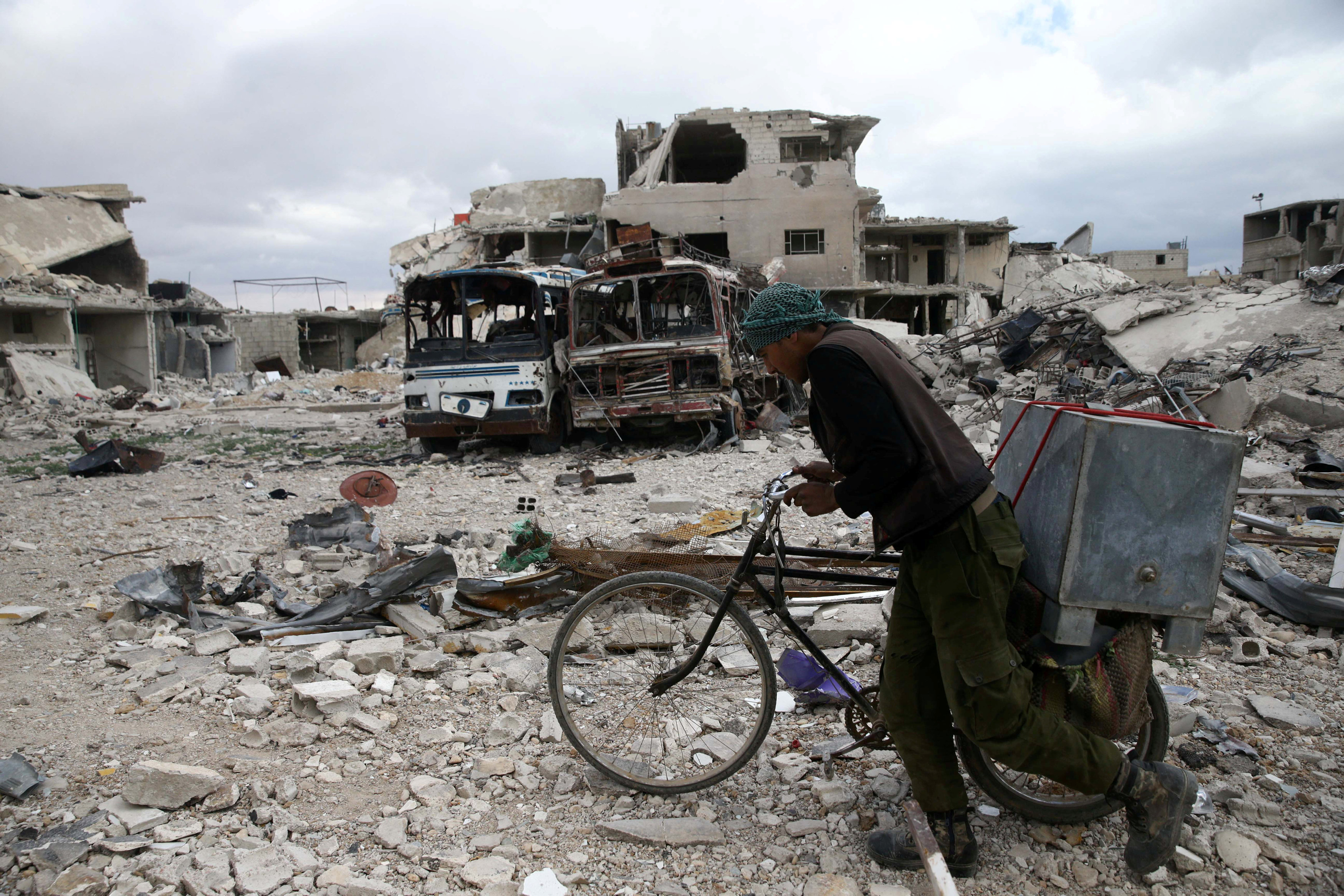 A man walks with his bicycle at a damaged site in the besieged town of Douma, Eastern Ghouta, in Damascus, Syria March 30, 2018. REUTERS/Bassam Khabieh