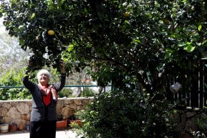 Holocaust survivor Betty Kazin Rosenbaum, 76, stands under a tree in her garden in Zichron Yaakov, Israel, April 10, 2018. REUTERS/Nir Elias