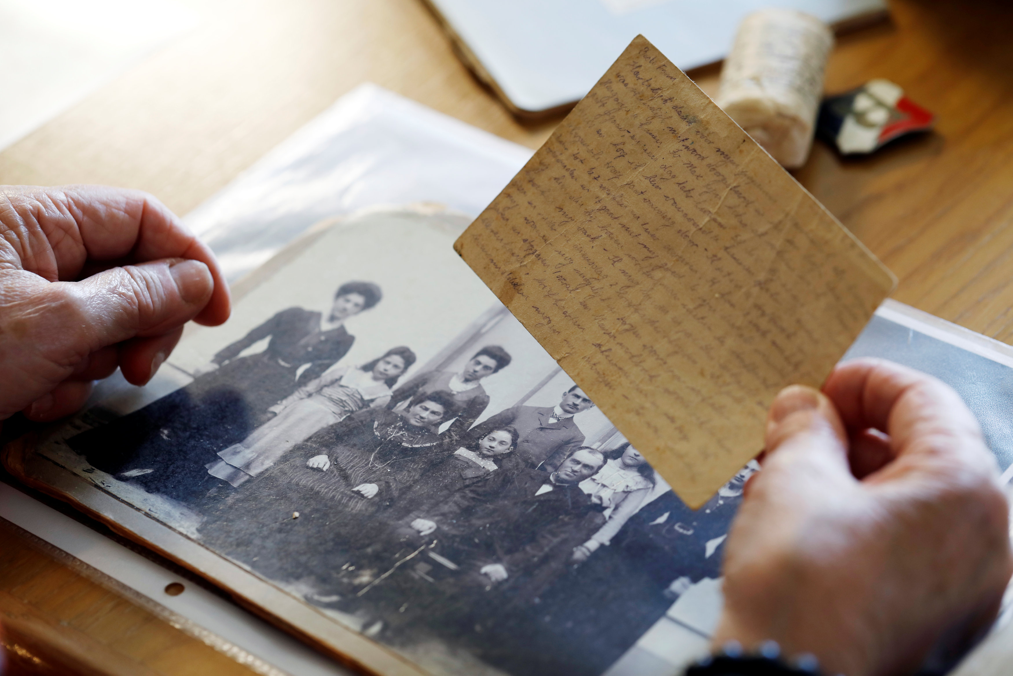 Holocaust survivor Betty Kazin Rosenbaum, 76, holds an old letter and a family photo during an interview in her house in Zichron Yaakov, Israel, April 10, 2018. Picture taken April 10, 2018. REUTERS/Nir Elias