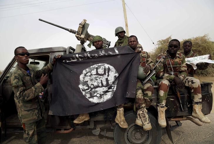 FILE PHOTO: Nigerian soldiers hold up a Boko Haram flag that they had seized in the recently retaken town of Damasak, Nigeria, March 18, 2015. REUTERS/Emmanuel Braun/File Photo