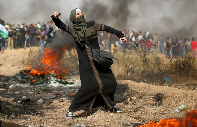 A girl hurls stones during clashes with Israeli troops at a protest where Palestinians demand the right to return to their homeland, at the Israel-Gaza border, east of Gaza City, April 13, 2018. REUTERS/Mohammed Salem