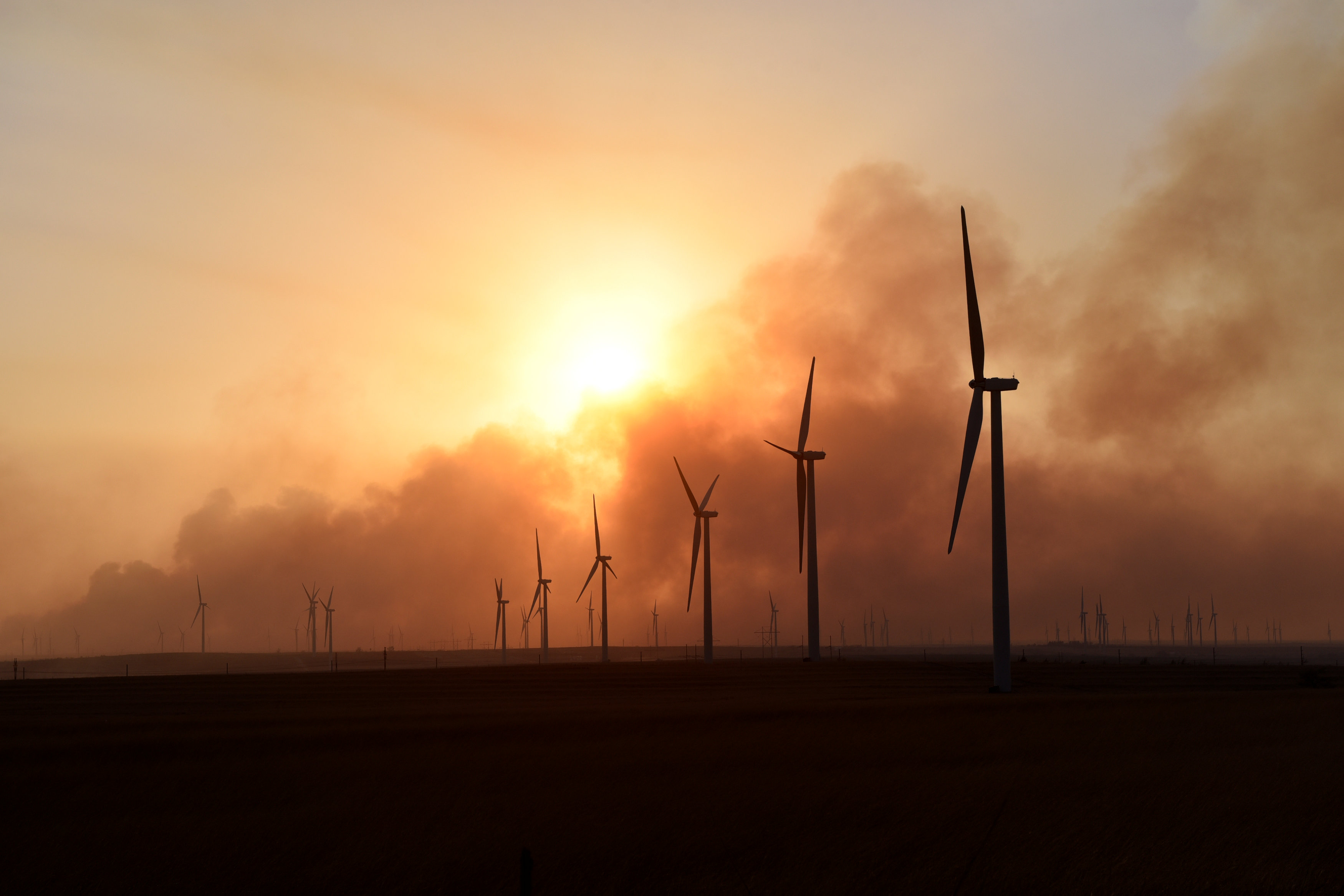 The sun sets through smoke from the Rhea fire on a wind farm near Seiling, Oklahoma, U.S. April 17, 2018. REUTERS/Nick Oxford