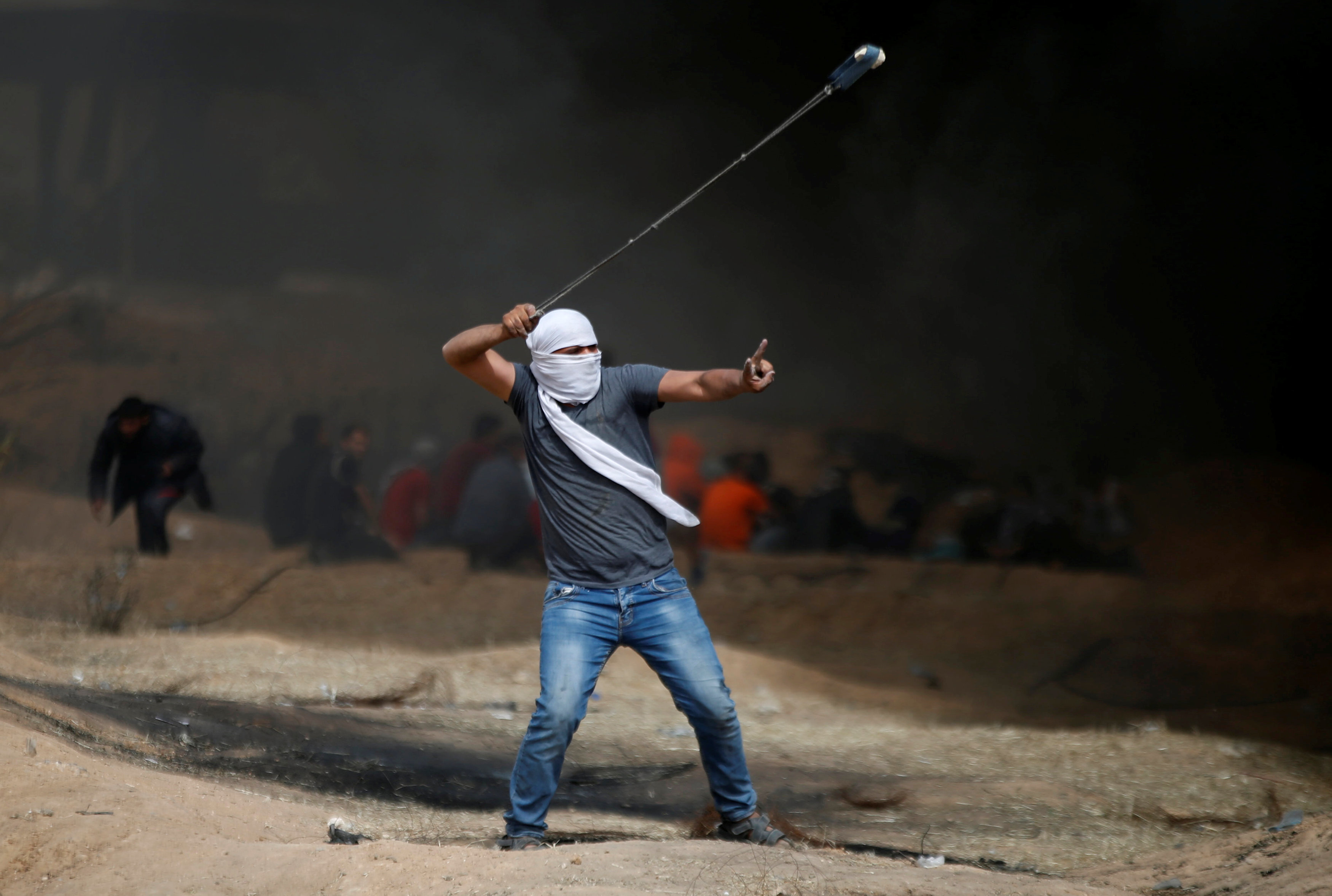 A demonstrator gestures as he hurls stones during clashes with Israeli troops at a protest at the Israel-Gaza border where Palestinians demand the right to return to their homeland, east of Gaza City April 20, 2018. REUTERS/Mohammed Salem