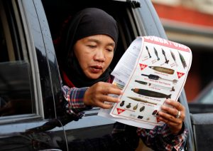 A woman reads a document at a military checkpoint before residents were allowed to return to their homes for the first time since the battle between government troops and Islamic State militants began in May last year, in the Islamic city of Marawi, southern Philippines April 19, 2018. REUTERS/Erik De Castro