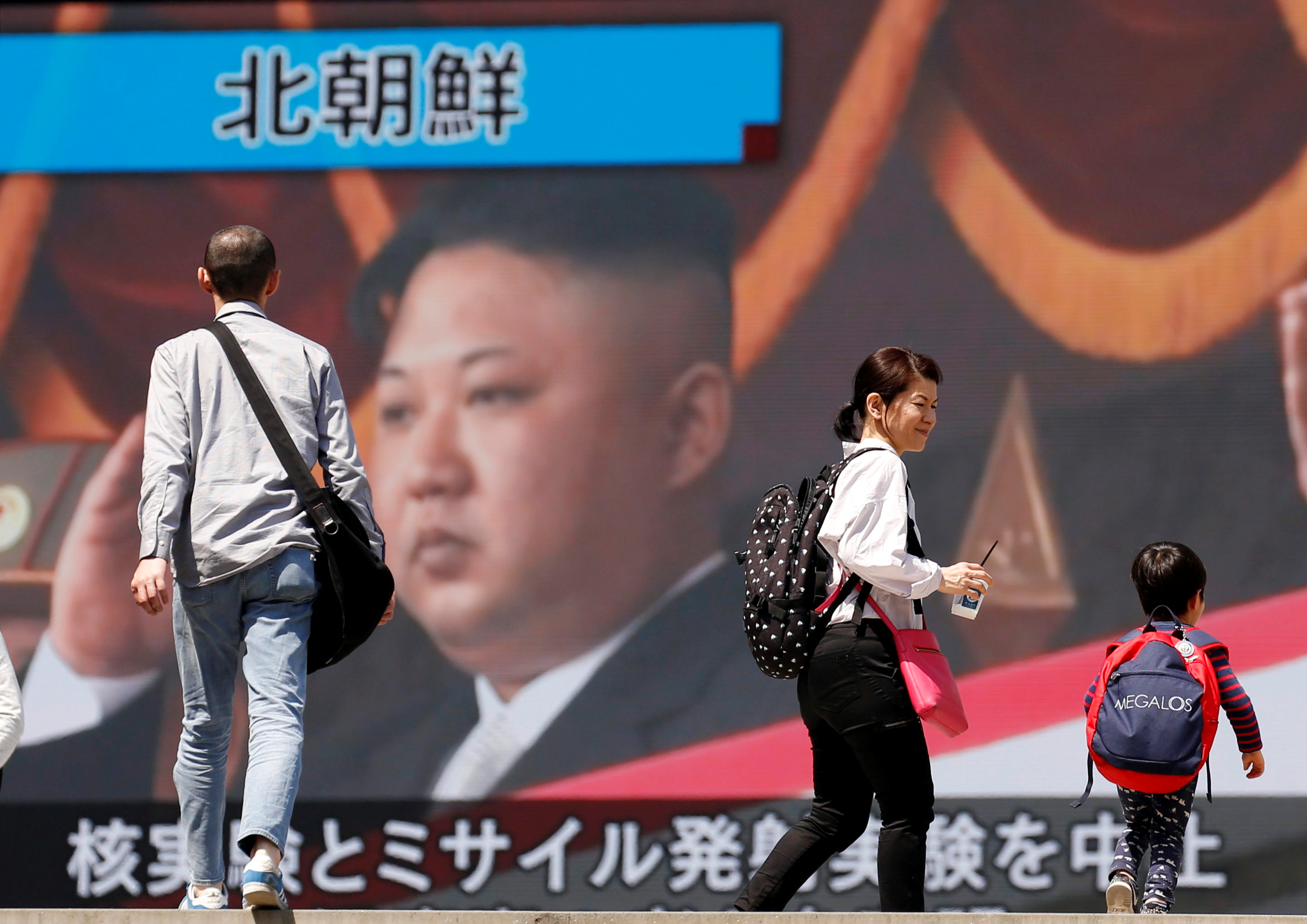 People walk past a street monitor showing North Korea's leader Kim Jong Un in a news report about North Korea's announcement, in Tokyo, Japan, April 21, 2018. REUTERS/Toru Hanai