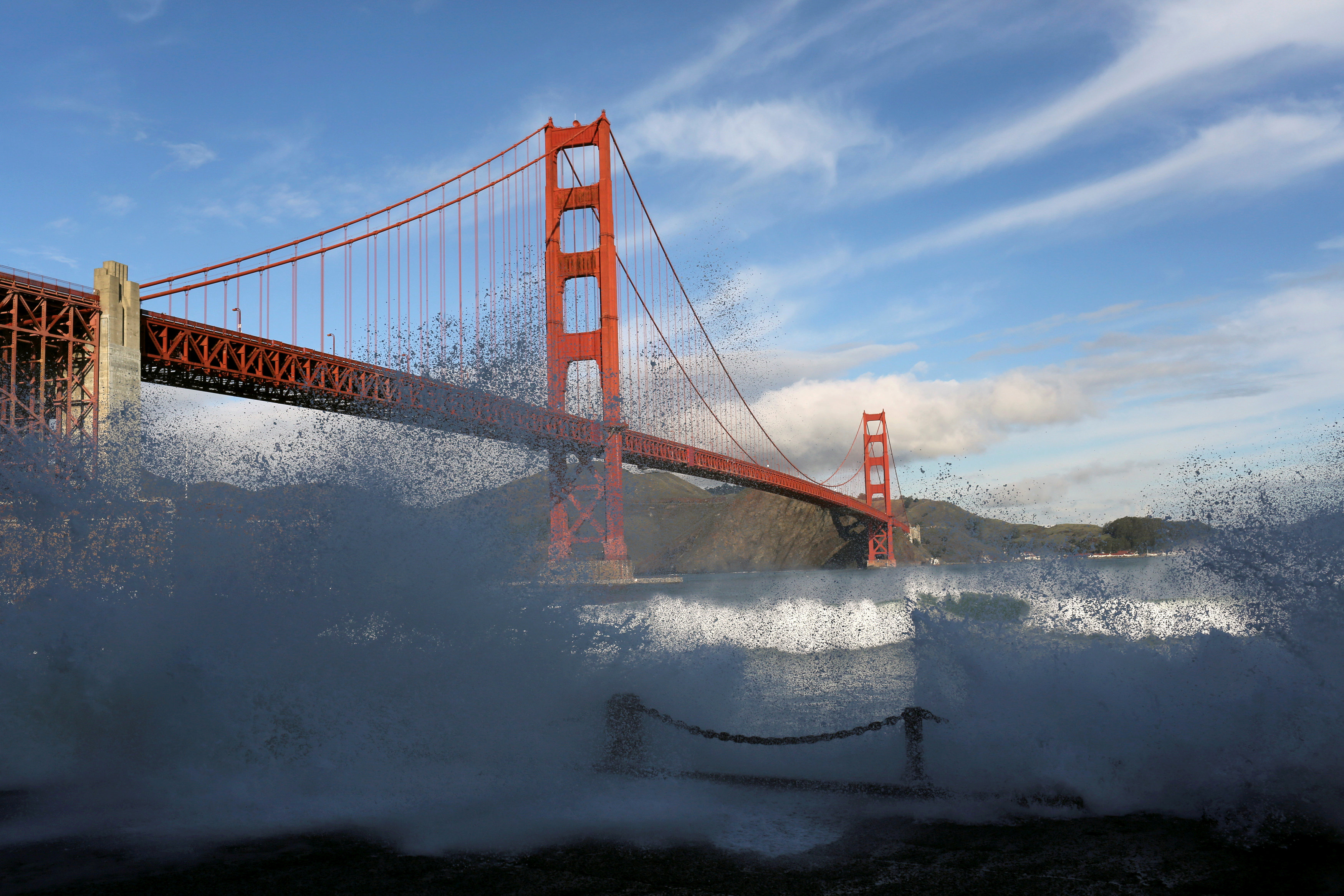 FILE PHOTO: Waves crash against a sea wall in San Francisco Bay beneath the Golden Gate Bridge in San Francisco, California, December 16, 2014. REUTERS/Robert Galbraith//File Photo