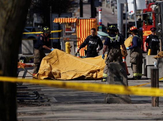 Firemen cover a victim of an incident where a van struck multiple people at a major intersection in Toronto's northern suburbs, in Toronto, Ontario, Canada, April 23, 2018. REUTERS/Carlo Allegri