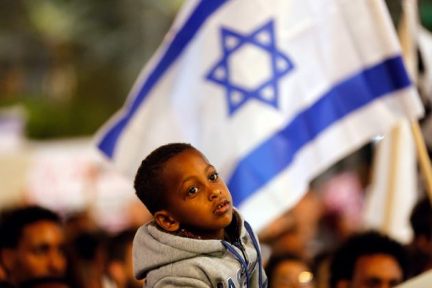 FILE PHOTO: A boy takes part in a protest against the Israeli government's plan to deport African migrants, in Tel Aviv, Israel March 24, 2018. REUTERS/Corinna Kern/File Photo