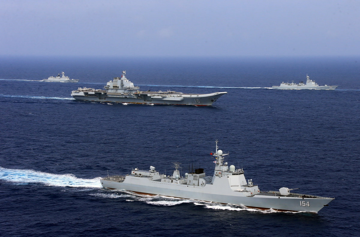 FILE PHOTO - China's aircraft carrier Liaoning (C) takes part in a military drill of Chinese People's Liberation Army (PLA) Navy in the western Pacific Ocean, April 18, 2018. Picture taken April 18, 2018. REUTERS/Stringer