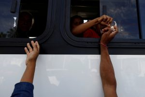 A group of Central American migrants, moving in a caravan through Mexico, ask for money to get on a microbus to the office of Mexico's National Institute of Migration to start the legal process and get temporary residence status for humanitarian reasons, in Hermosillo, Sonora state, Mexico April 24, 2018. REUTERS/Edgard Garrido