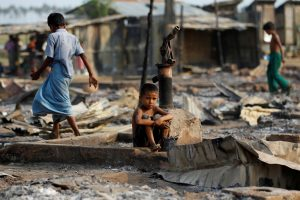 FILE PHOTO: A boy sits in a burnt area after fire destroyed shelters at a camp for internally displaced Rohingya Muslims in the western Rakhine State near Sittwe, Myanmar May 3, 2016. REUTERS/Soe Zeya Tun/File Phot