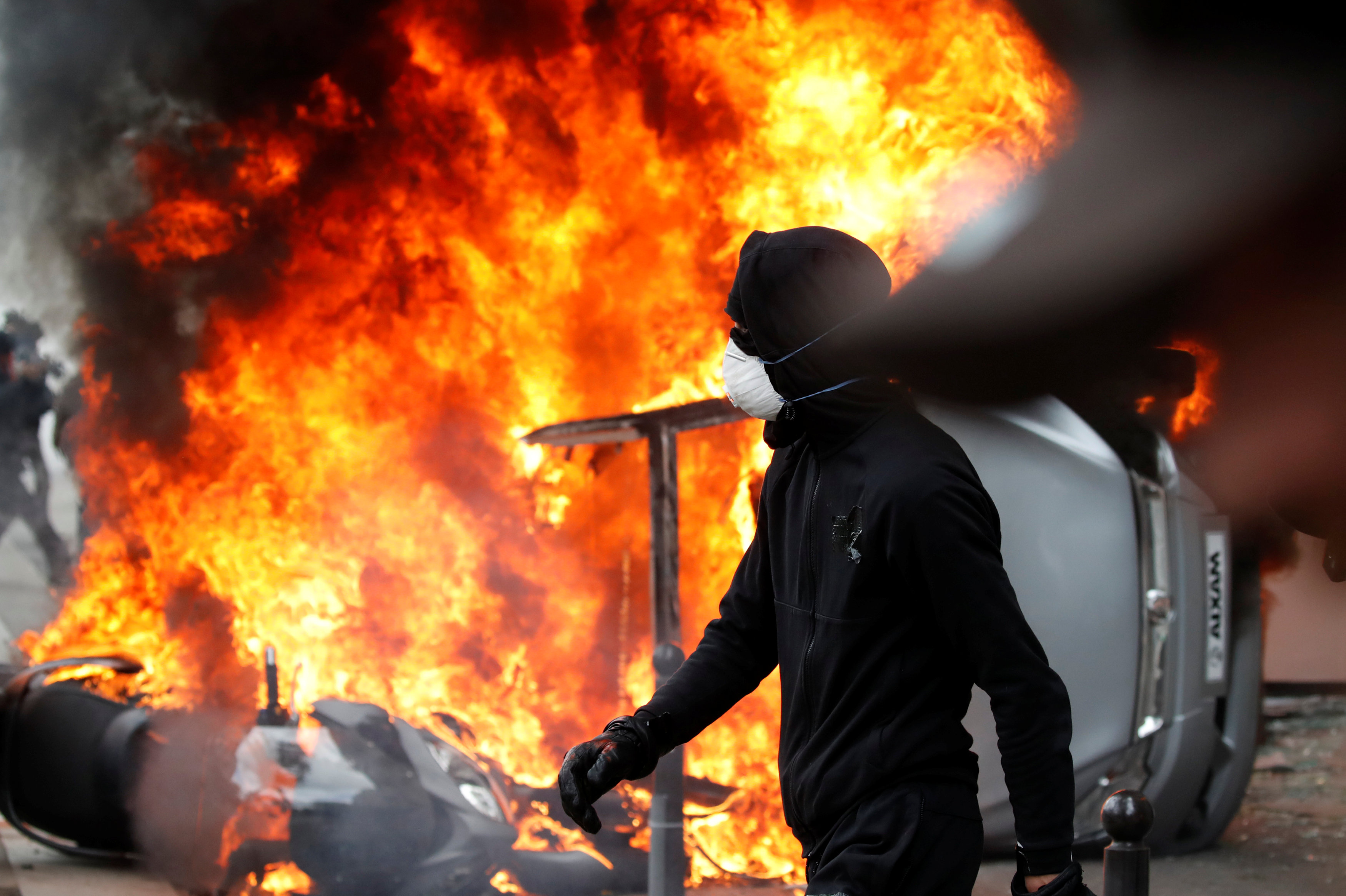 A masked protester walks near a car that burns outside a Renault automobile garage during clashes during the May Day labour union march in Paris, France, May 1, 2018. REUTERS/Christian Hartmann