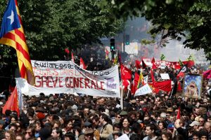 """People hold a banner which reads, """"Students, Employees. Everyone in the Street. General Strike"""" during the traditional May Day labour union march in Paris, France, May 1, 2018. REUTERS/Christian Hartmann"""