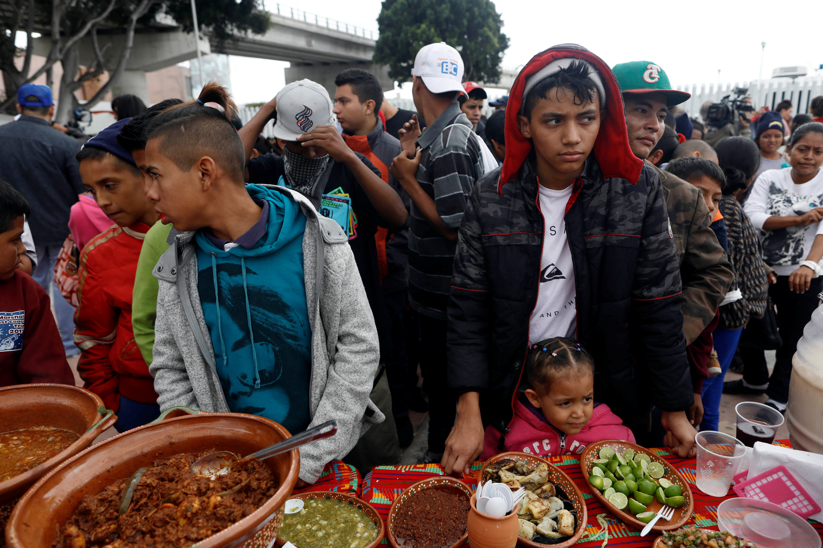 Members of a caravan of migrants from Central America line up to receive food near the San Ysidro checkpoint as the first fellow migrants entered U.S. territory to seek asylum on Monday, in Tijuana, Mexico April 30, 2018. REUTERS/Edgard Garrido