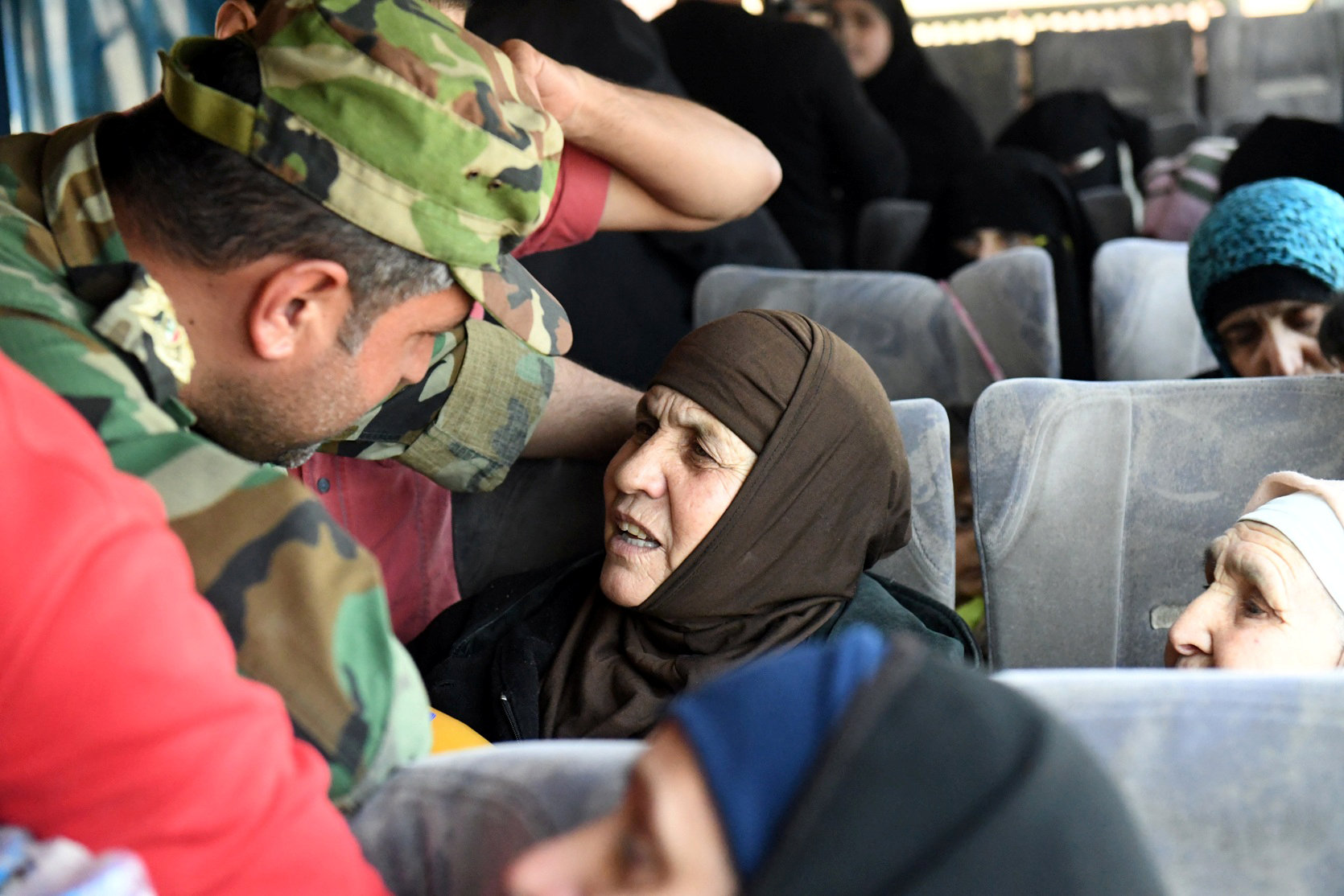 A soldier loyal to Syria's President Bashar al Assad forces talks to a woman in a bus after they were released by militants from Idlib, Syria May 1, 2018. SANA/Handout via REUTERS