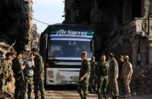 Soldiers loyal to Syria's President Bashar al Assad are seen near a bus carrying rebels from Yarmouk Palestinian camp in Damascus, Syria April 30, 2018. SANA/ via REUTERS