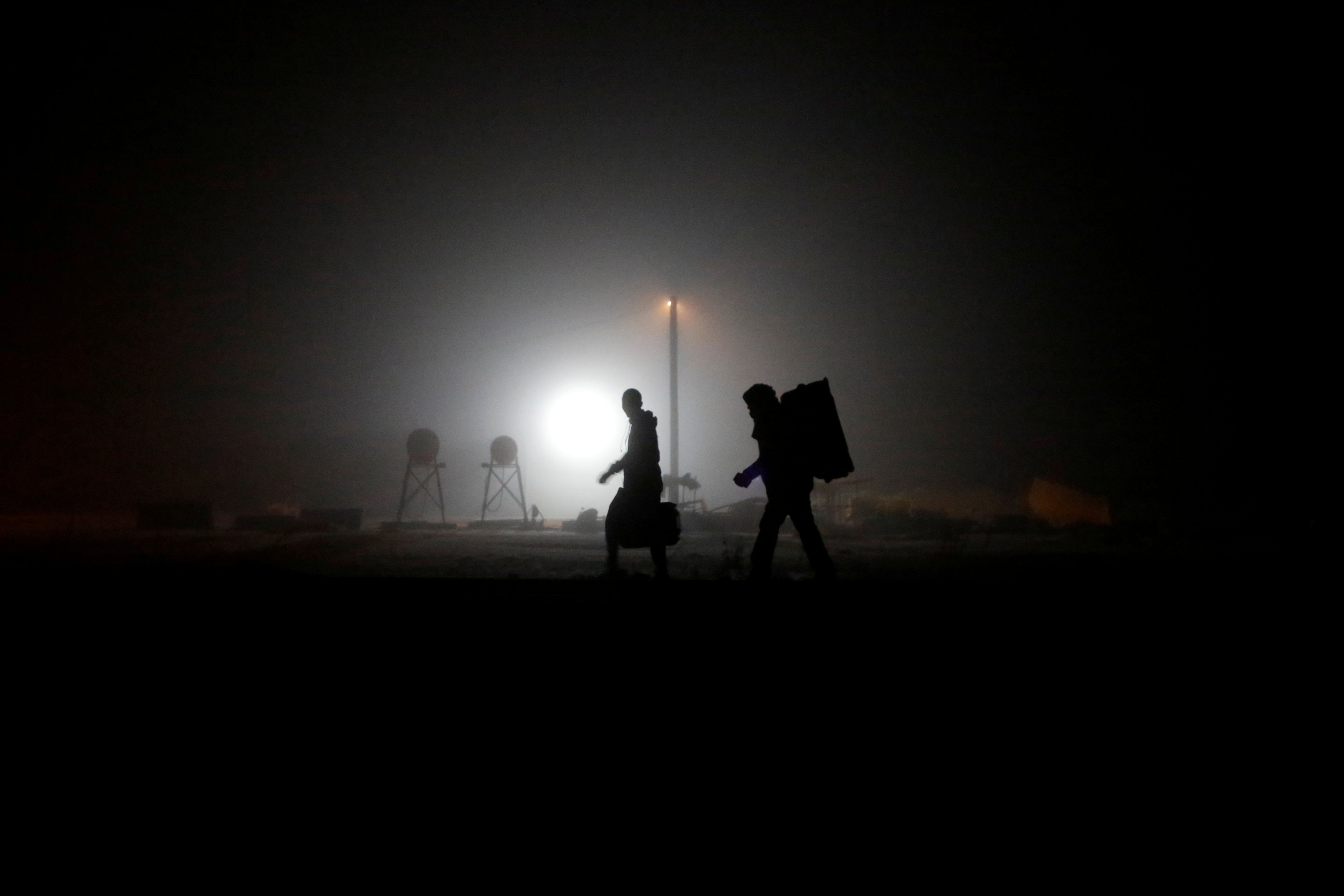 FILE PHOTO: A group of migrants who said they were from Djibouti and Somalia walk along railway tracks after crossing the Canada-U.S. border in Emerson, Manitoba, Canada, March 27, 2017. REUTERS/Chris Wattie/File Photo