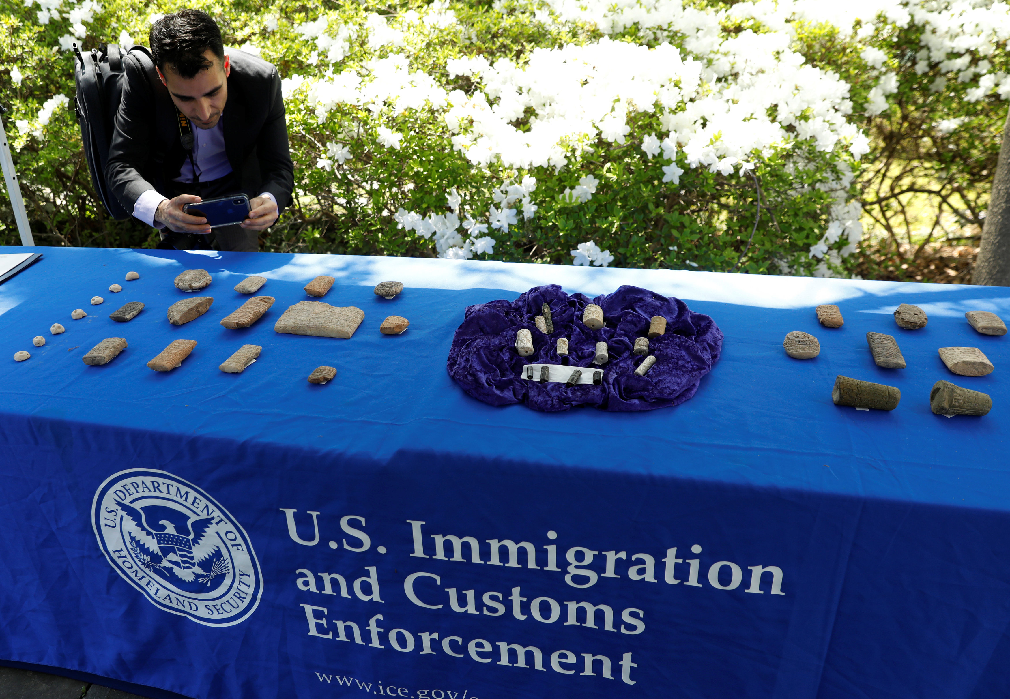 A man photographs artifacts on display, as U.S. Immigration and Customs Enforcement (ICE) hosts an event to return several thousand ancient artifacts to the Republic of Iraq, at the Iraqi ambassador's residence in Washington, DC, U.S., May 2, 2018. REUTERS/Kevin Lamarque