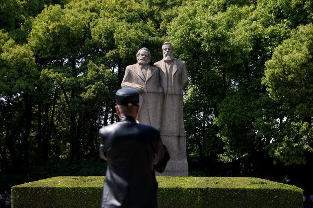 A man walks in front of the statue of German philosophers Karl Marx and Friedrich Engels at a park in Shanghai, China May 3, 2018. REUTERS/Aly Song