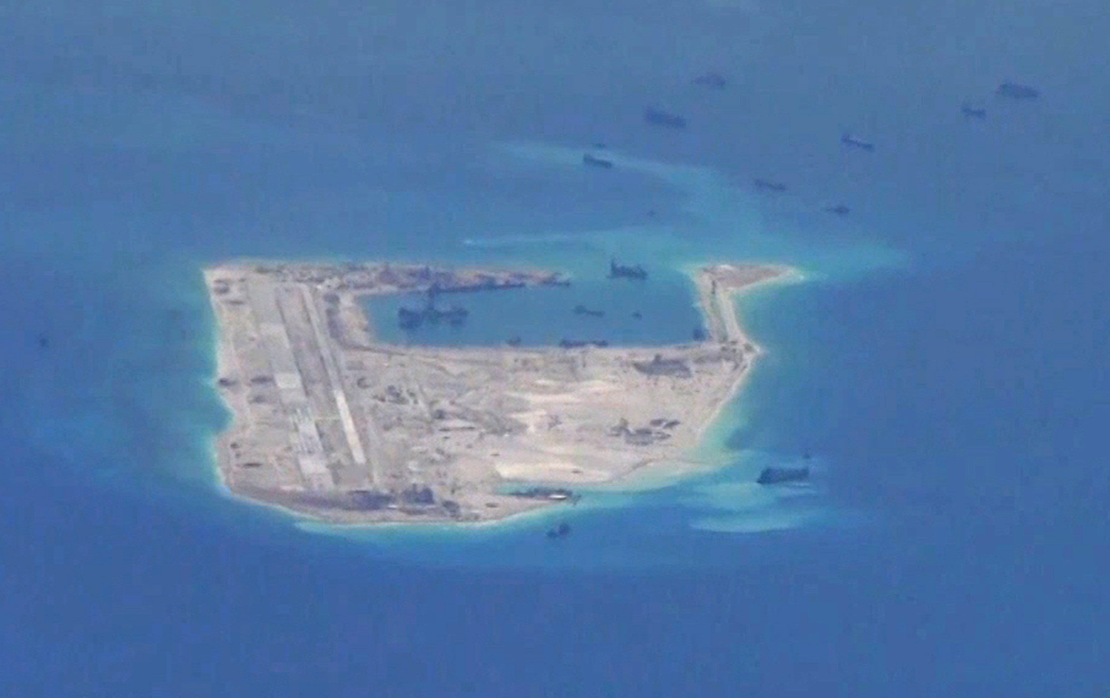 FILE PHOTO: Chinese dredging vessels are purportedly seen in the waters around Fiery Cross Reef in the disputed Spratly Islands in the South China Sea in this still image from video taken by a P-8A Poseidon surveillance aircraft provided by the United States Navy May 21, 2015. U.S. Navy/Handout via Reuters/File Photo