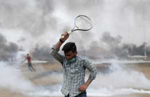 A demonstrator uses a racket to return tear gas canisters fired by Israeli troops during a protest where Palestinians demand the right to return to their homeland, at the Israel-Gaza border in the southern Gaza Strip, May 4, 2018. REUTERS/Ibraheem Abu Mustafa