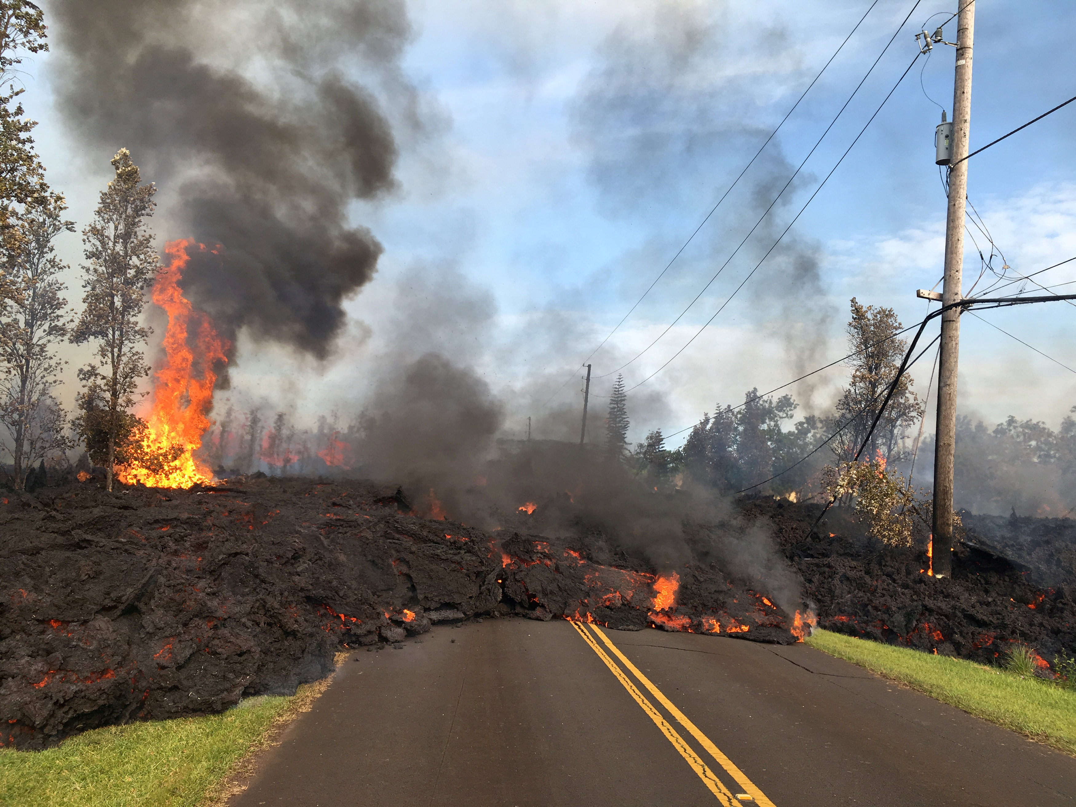 Lava advances along a street near a fissure in Leilani Estates, on Kilauea Volcano's lower East Rift Zone, Hawaii, the U.S., May 5, 2018. U.S. Geological Survey/Handout via REUTERS