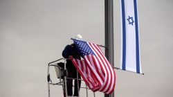 A worker on a crane hangs a U.S. flag next to an Israeli flag, next to the entrance to the U.S. consulate in Jerusalem, May 7, 2018. REUTERS/Ronen Zvulun/File Photo