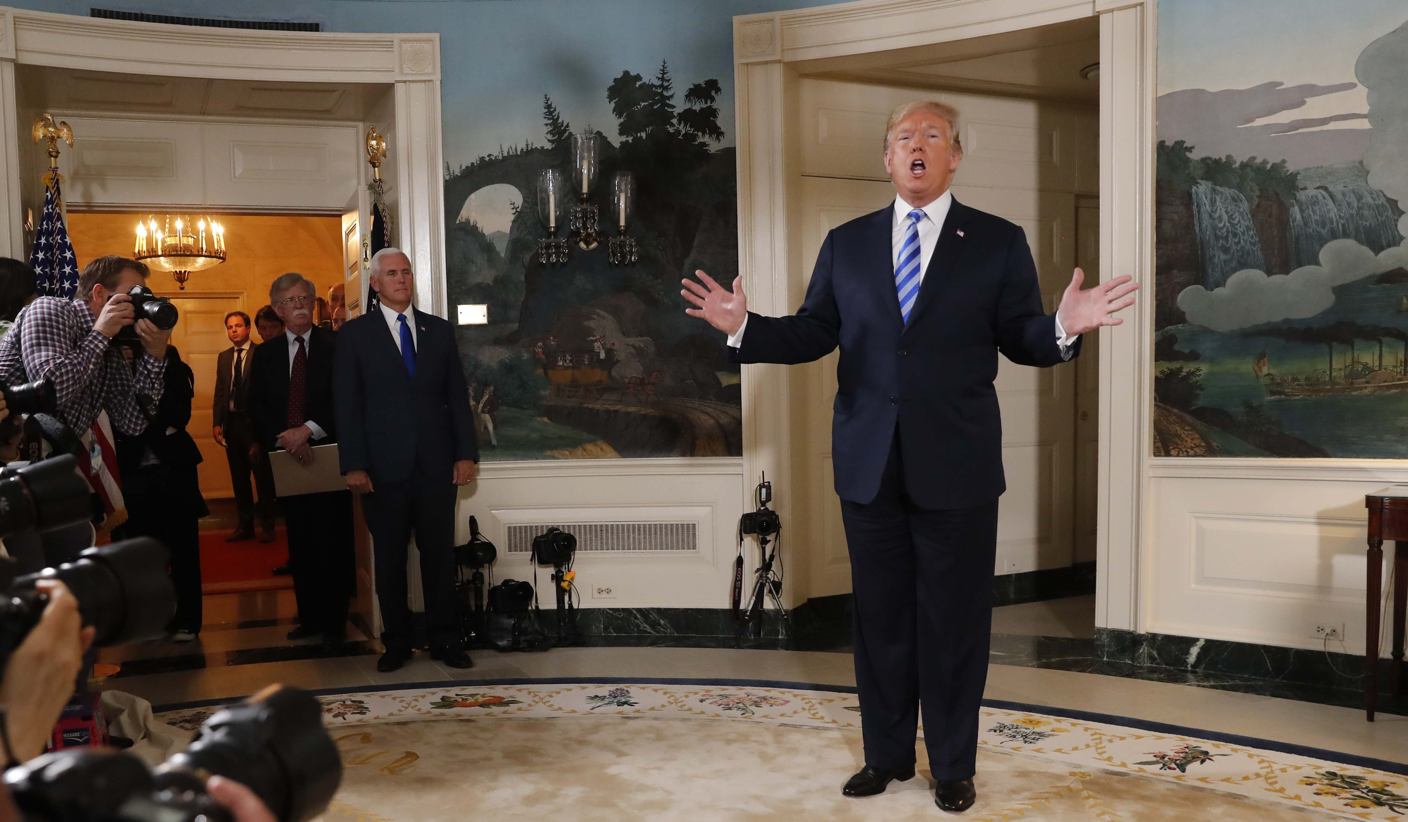 U.S. President Donald Trump reacts to a question from the media as National Security Advisor John Bolton and Vice President Mike Pence look on after the president announced his intention to withdraw from the JCPOA Iran nuclear agreement during a statement in the Diplomatic Room at the White House in Washington, U.S., May 8, 2018. REUTERS/Jonathan Ernst
