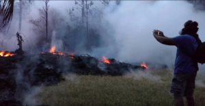 A man wearing a gas mask takes pictures of a lava fissure in Leilani Estates, Hawaii, U.S. May 9, 2018, in this still image taken from a social media video. Apau Hawaii Tours/Social Media via REUTERS