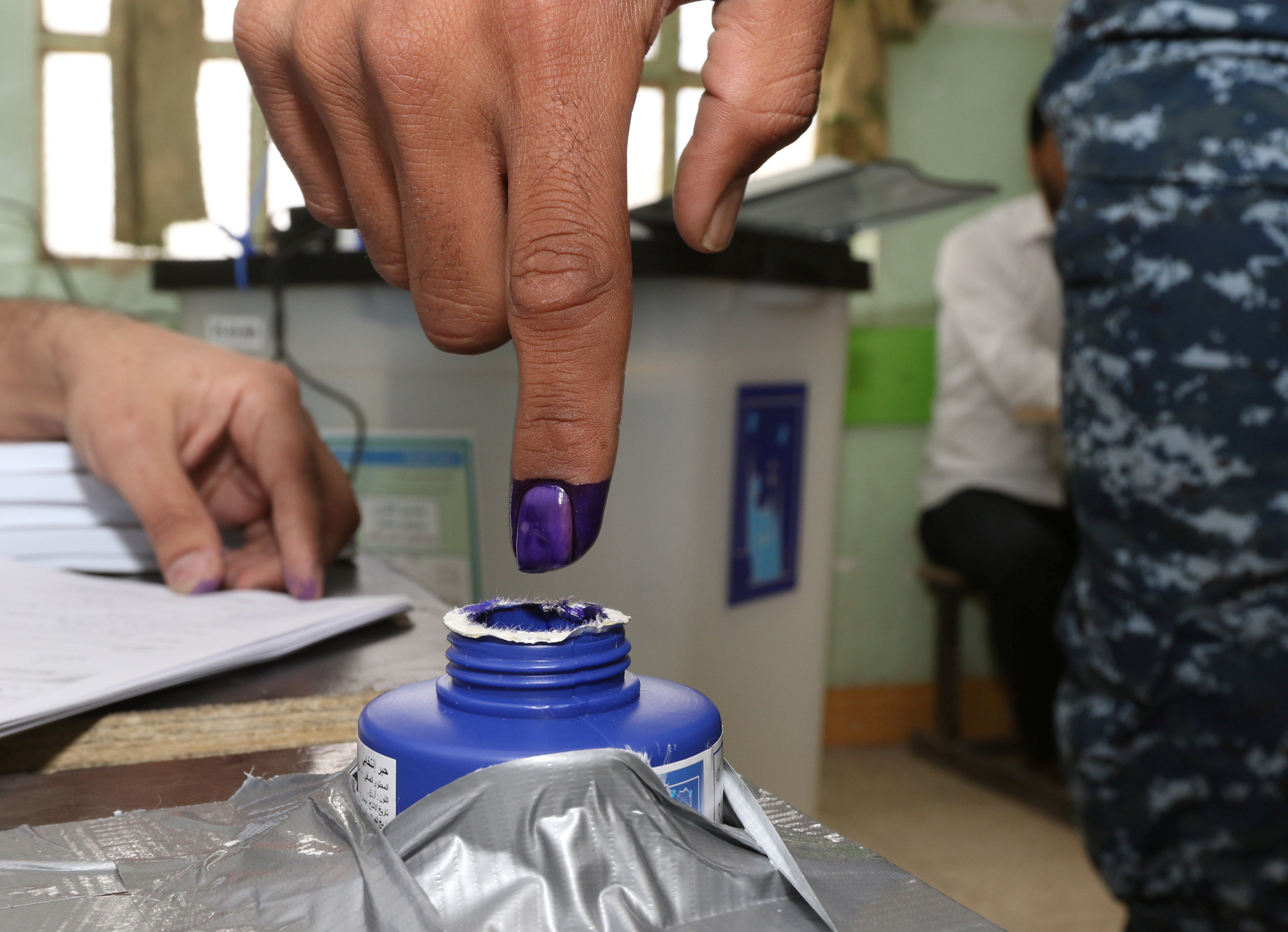 An Iraqi security member dips his finger in ink after casting his vote at a polling station, two days before polls open to the public in a parliamentary election in Kirkuk, Iraq May 10, 2018. REUTERS/Ako Rasheed