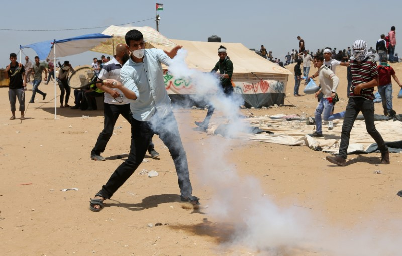 A demonstrator uses a racket to return a tear gas canister fired by Israeli troops during a protest where Palestinians demand the right to return to their homeland, at the Israel-Gaza border in the southern Gaza Strip, May 11, 2018. REUTERS/Ibraheem Abu Mustafa
