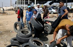 A Palestinian woman drops tyres to be burnt at the Israel-Gaza border during a protest where Palestinians demand the right to return to their homeland, in the southern Gaza Strip May 11, 2018. REUTERS/Ibraheem Abu Mustafa