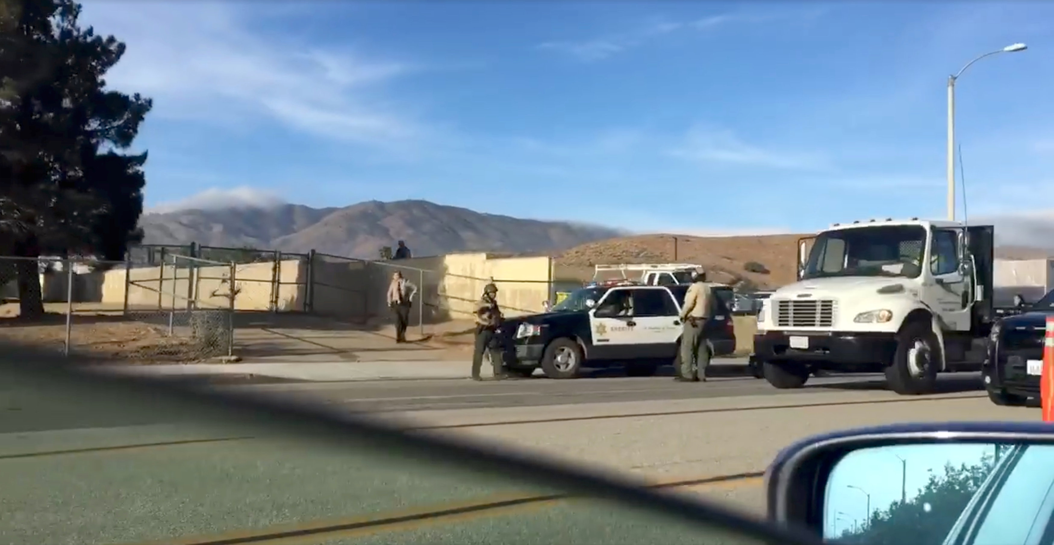 Police vehicles are seen on the road near Highland High School, in Palmdale, California, U.S., May 11, 2018 in this picture grab obtained from social media video. MELENDEZ N JUNIOR/via REUTERS