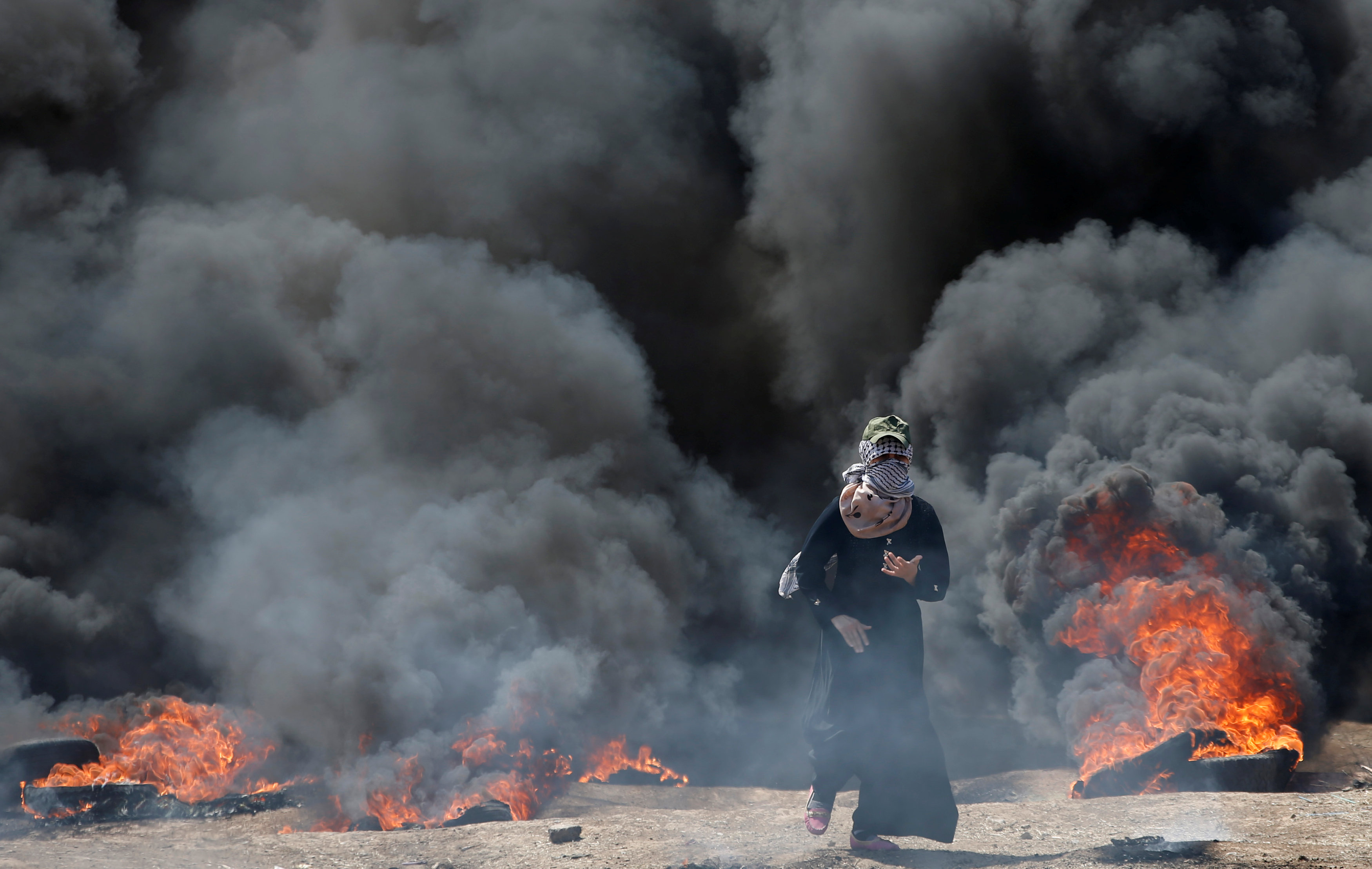 A female Palestinian demonstrator gestures during a protest against U.S. embassy move to Jerusalem and ahead of the 70th anniversary of Nakba, at the Israel-Gaza border, east of Gaza City May 14, 2018. REUTERS/Mohammed Salem