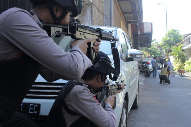 Police aim their weapons at a man who was being searched by other police officers following an explosion at nearby police headquarters in Surabaya, Indonesia May 14, 2018 in this photo taken by Antara Foto. Antara Foto/ Didik Suhartono / via REUTERS