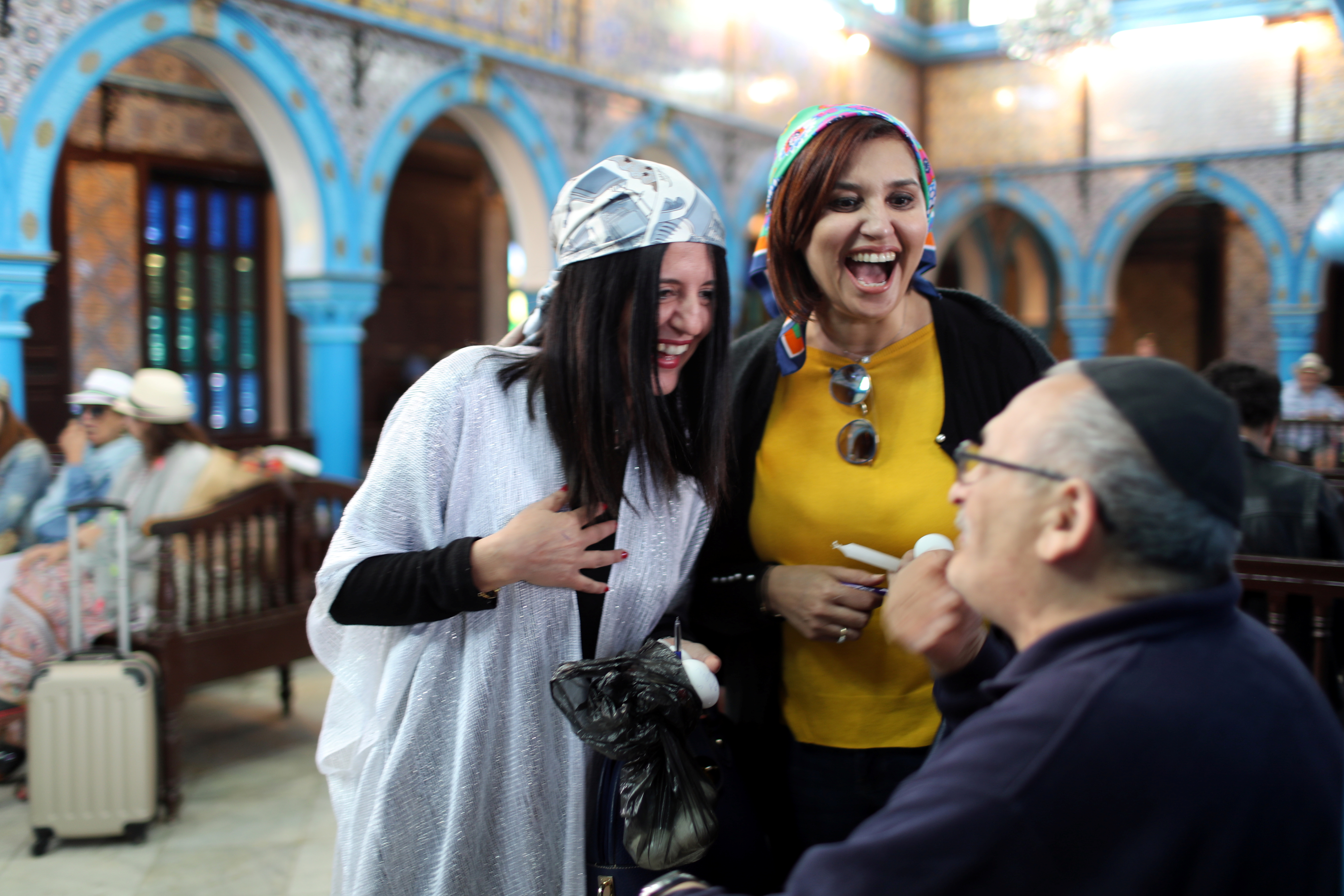 Two Tunisian Muslim women chat with a Jewish man at Ghriba, the oldest Jewish synagogue in Africa, during an annual pilgrimage in Djerba, Tunisia May 2, 2018. Picture taken May 2, 2018. REUTERS/Ahmed Jadallah