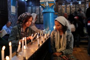 Cyrine Ben Said (L) and Amnia Ben Khalif, Muslim Tunisians, light candles during a religious ceremony at Ghriba, the oldest Jewish synagogue in Africa, during an annual pilgrimage in Djerba, Tunisia May 2, 2018. Picture taken May 2, 2018. REUTERS/Ahmed Jadallah