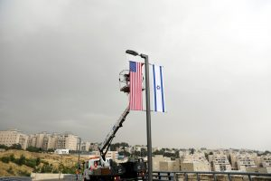 FILE PHOTO: A worker on a crane hangs a U.S. flag next to an Israeli flag, next to the entrance to the U.S. consulate in Jerusalem, May 7, 2018. REUTERS/Ronen Zvulun/File Photo