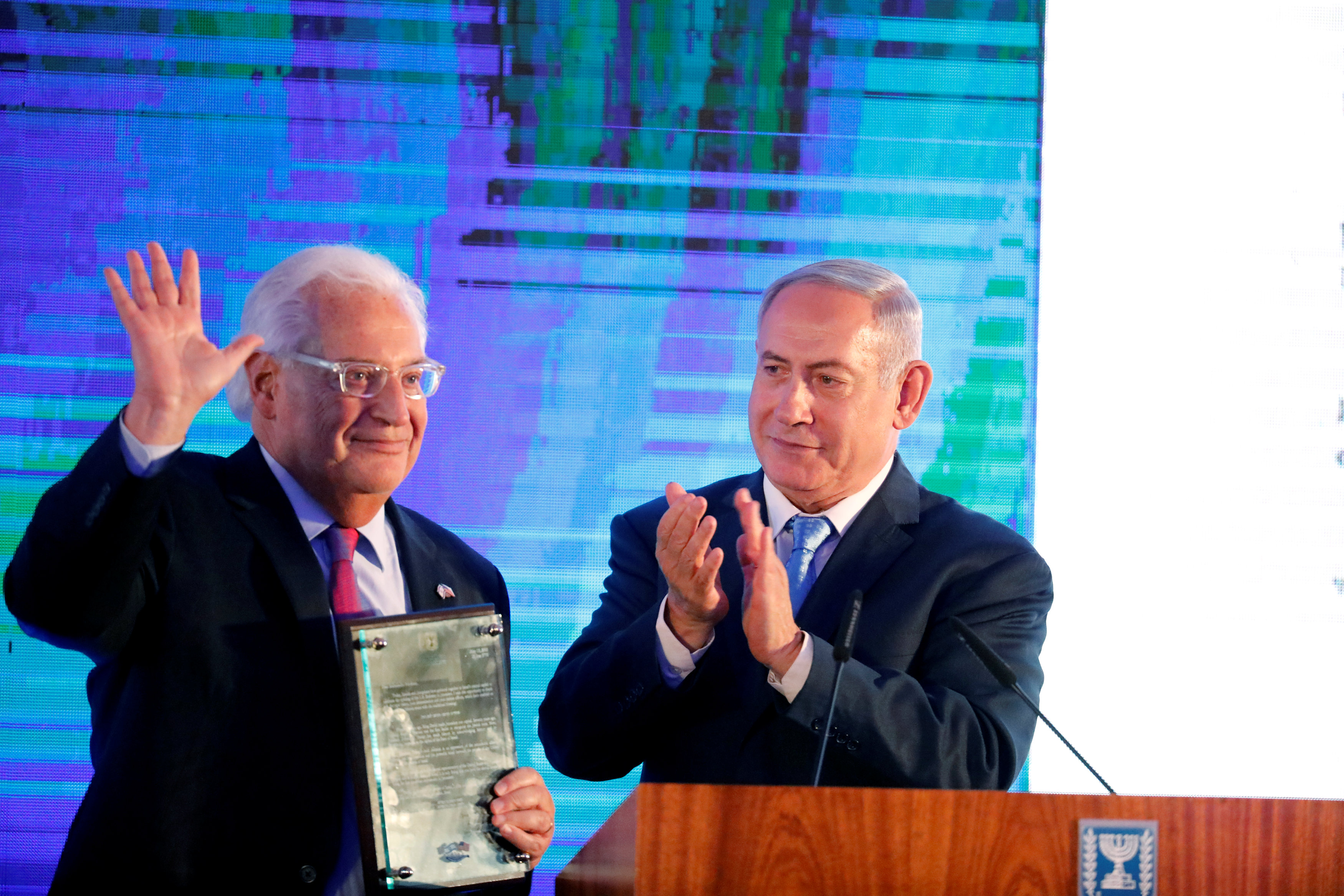 Israeli Prime Minister Benjamin Netanyahu claps after handing U.S. Ambassador to Israel David Friedman a letter of appreciation, during a reception held at the Israeli Ministry of Foreign Affairs in Jerusalem, ahead of the moving of the U.S. embassy to Jerusalem, May 13, 2018. REUTERS/Amir Cohen
