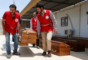 Libyan Red Crescent workers carry coffins, containing the remains of the bodies of Egyptian Copts killed by Islamic State in Sirte, which are to be transferred to Egypt after the forensic tests were completed and the bodies identified, at a morgue in Misrata, Libya May 14, 2018. REUTERS/Ismail Zitouny
