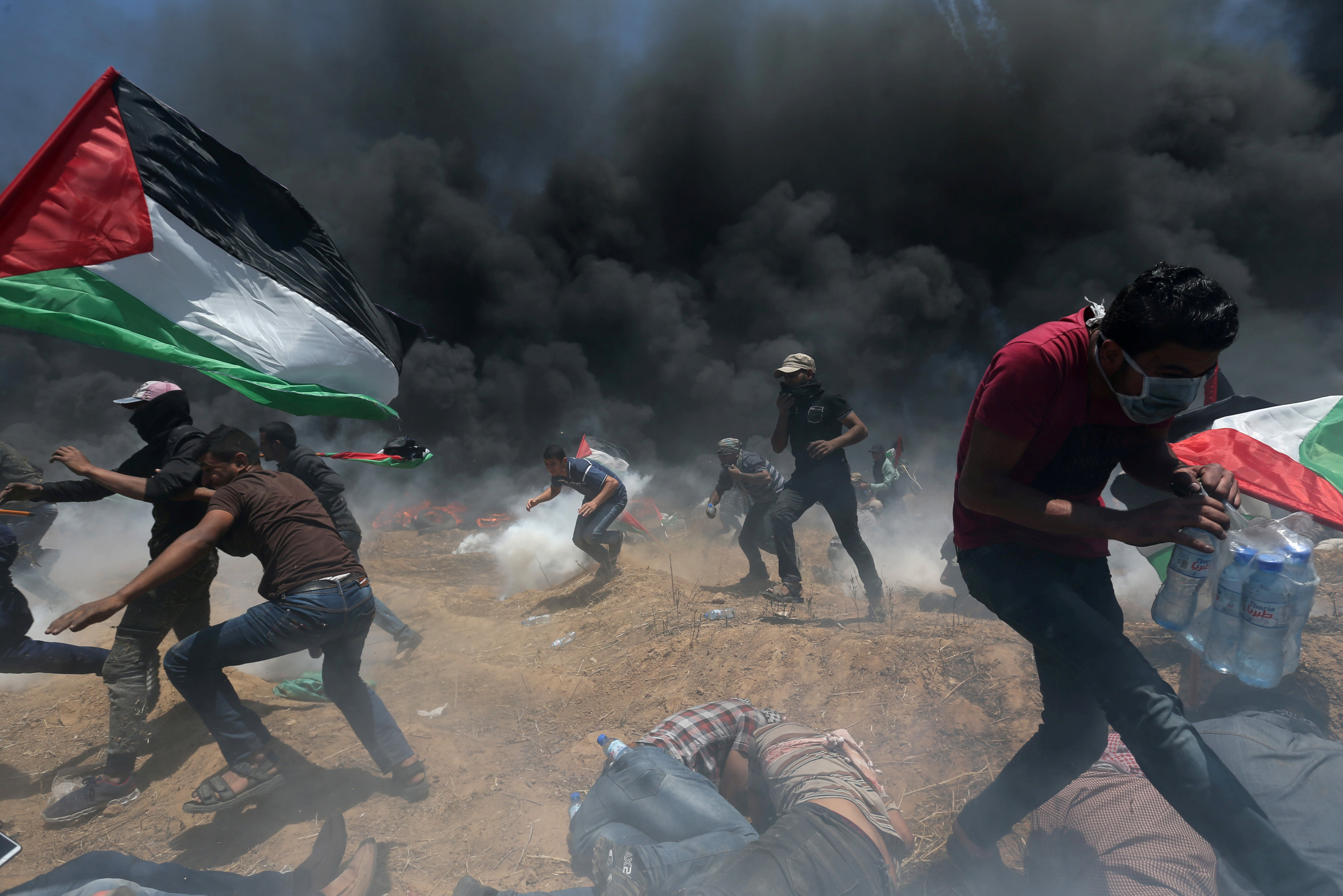 Palestinian demonstrators run for cover from Israeli fire and tear gas during a protest against U.S. embassy move to Jerusalem and ahead of the 70th anniversary of Nakba, at the Israel-Gaza border in the southern Gaza Strip May 14, 2018. REUTERS/Ibraheem Abu Mustafa