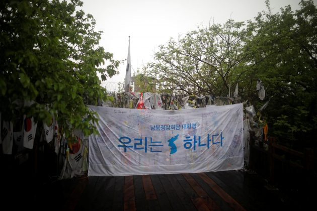 A banner bearing a unification flag hang on a barbed wire fence near the demilitarized zone separating the two Koreas, in Paju, South Korea, May 16, 2018. REUTERS/Kim Hong-Ji