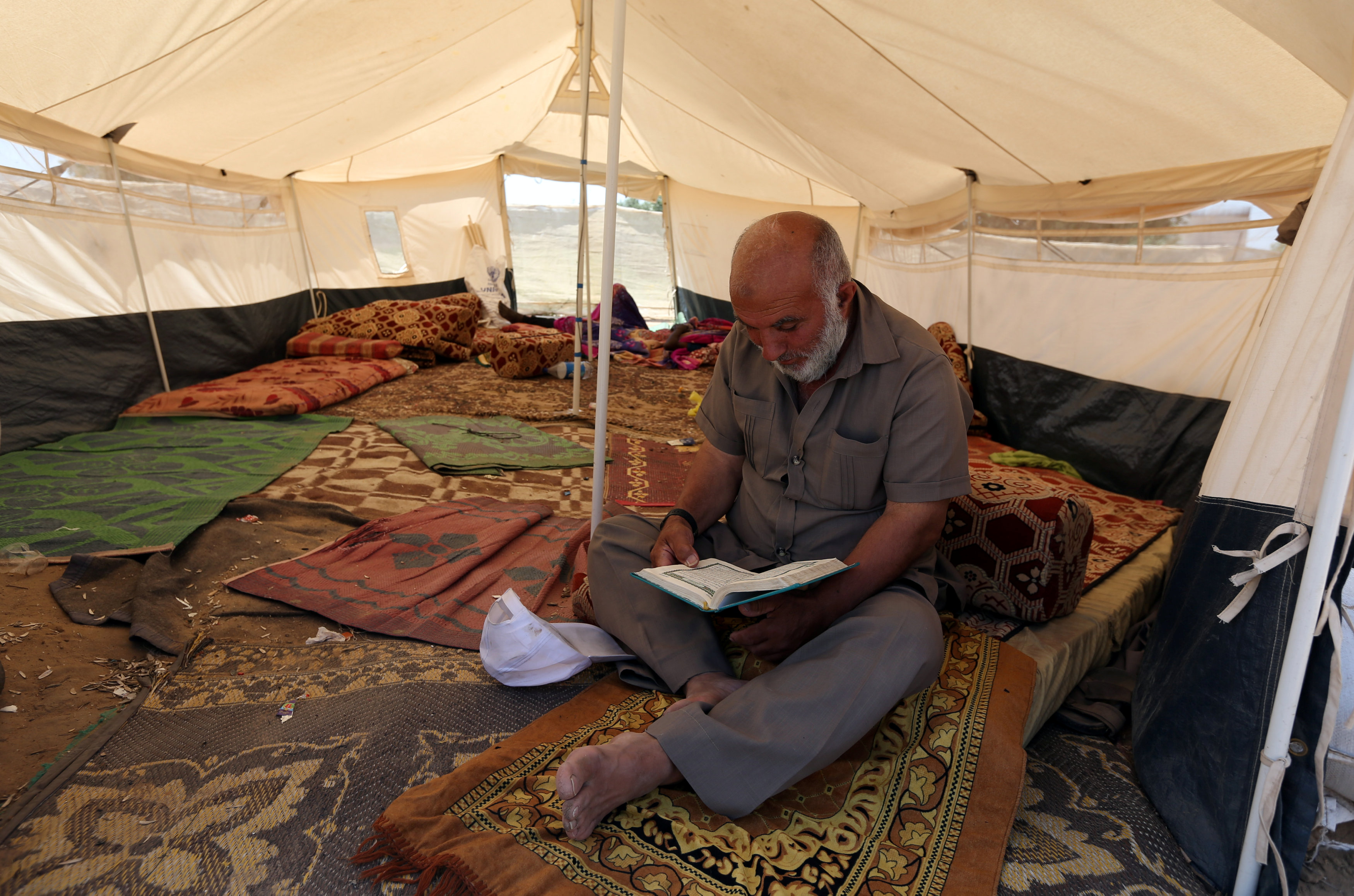 A Palestinian man reads the Koran inside a tent during the holy month of Ramadan, at a protest camp near the Israel-Gaza border in the central Gaza Strip May 17, 2018. REUTERS/Ibraheem Abu Mustafa